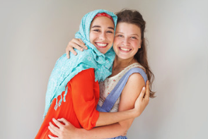 Two young women smiling and hugging